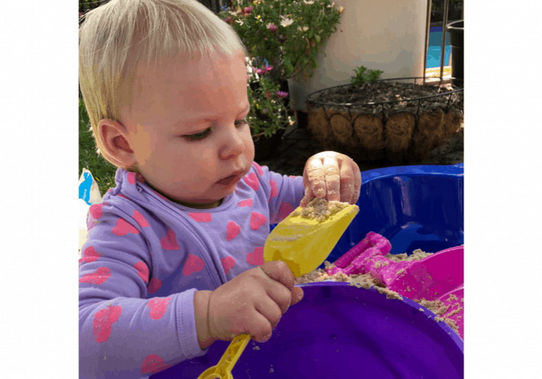 baby eating sand